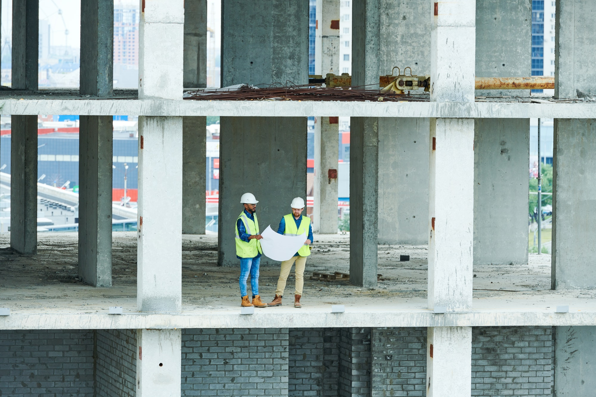 Construction engineers with draft in concrete building