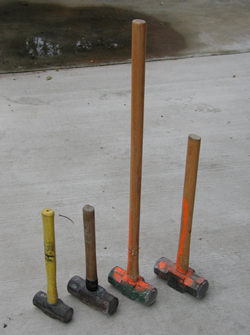 Multiple sledge hammers shown on a concrete pad to show the different handle lengths that are available