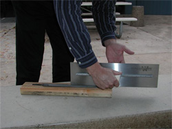 Trowel maintenance showing a board on the floor with a worker moving the trowel over it