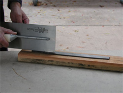 A worker shows how to move the trowel across a board to keep it sharp.