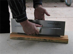 A cement mason shows off his trowel once it has been sharpened