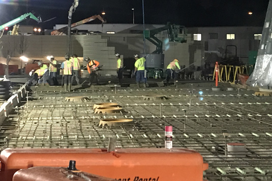 A night-time cement mason crew works on a job-site to build our world