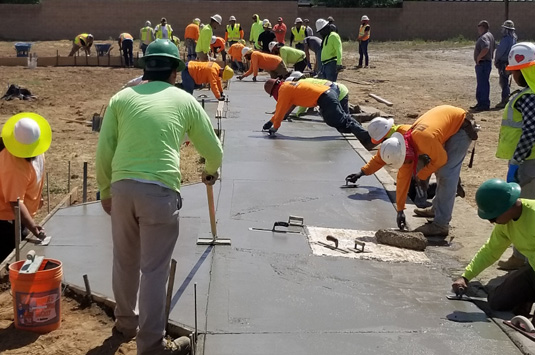 A group of cement masons learning how to construct a sidewalk as they are paid to learn